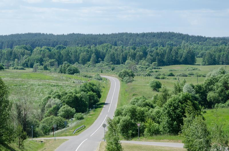 A hilly road in a summer day through fields, meadows and forests stock images