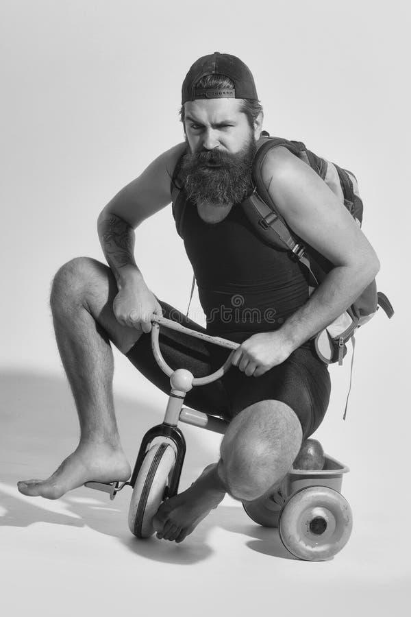 traveling hombre enojado barbudo con el bolso, manzana en el juguete de la bicicleta foto de archivo