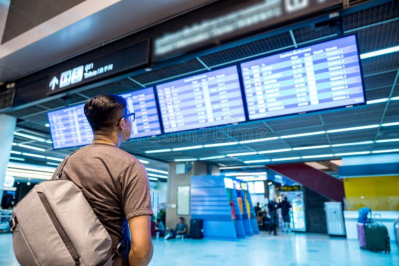 Traveling at international airport checking flight schedule. Flight schedule time table, Traveling at international airport checking flight schedule electronic royalty free stock photography