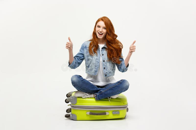 Traveling and Lifestyle concept. Young excited caucasian woman sitting on the luggage valise showing thumb up. Isolated stock image