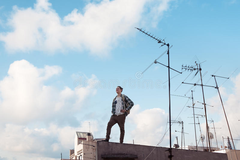 Traveling man standing on the roof, smiling and looking far away with bright blue sky and white clouds and antennas stock photos