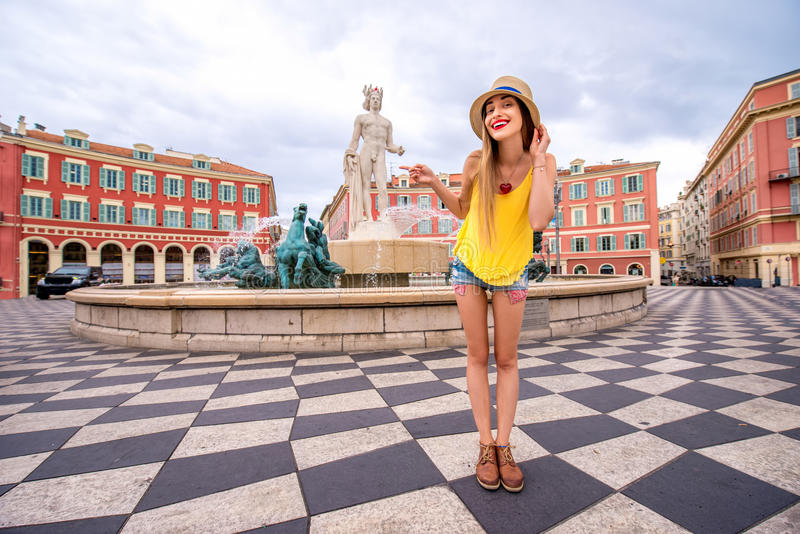 Traveling in Nice. Young female traveler photographing on the famous Apollo fountain background in Nice city in France royalty free stock image