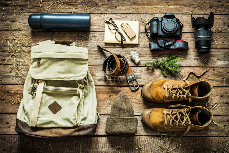 Traveling - packing preparing for adventure trip concept. Backpack, boots, hat, belt, thermos and camera on wooden background captured from above flat lay royalty free stock photo