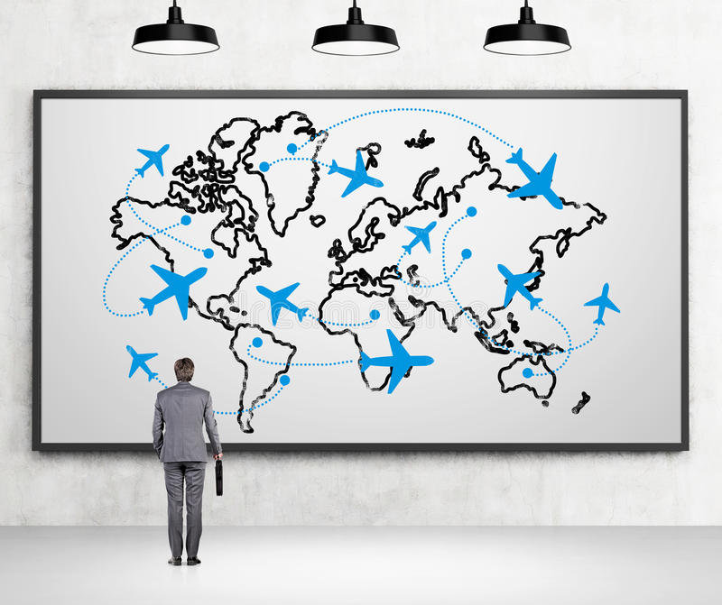 Traveling by plane. A man with a case standing in front of a map demonstaring flight destinations around the globe, three lamps above. Concrete background. Back stock photography