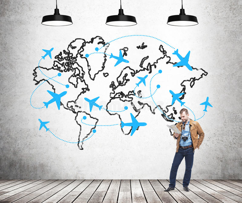 Traveling by plane stock image image of airport oxygen 66962879 a young man with a camera and a map standing in front of a concrete wall with a world map and planes drawn on it behind his back three lamps above gumiabroncs Gallery