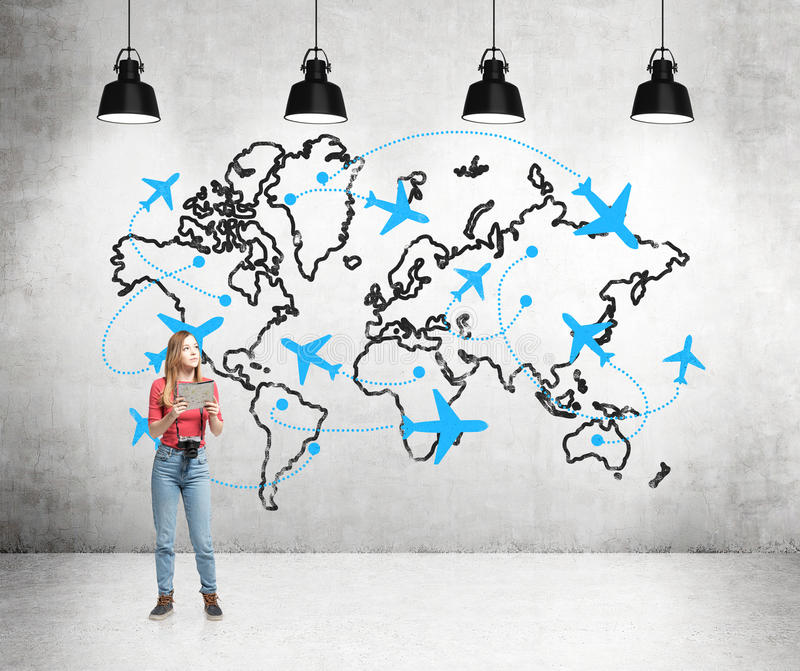 Traveling by plane stock photo image of jacket engine 66963052 a young woman with a camera and a map standing in front of a concrete wall with a world map and planes drawn on it behind her back four lamps above gumiabroncs Gallery