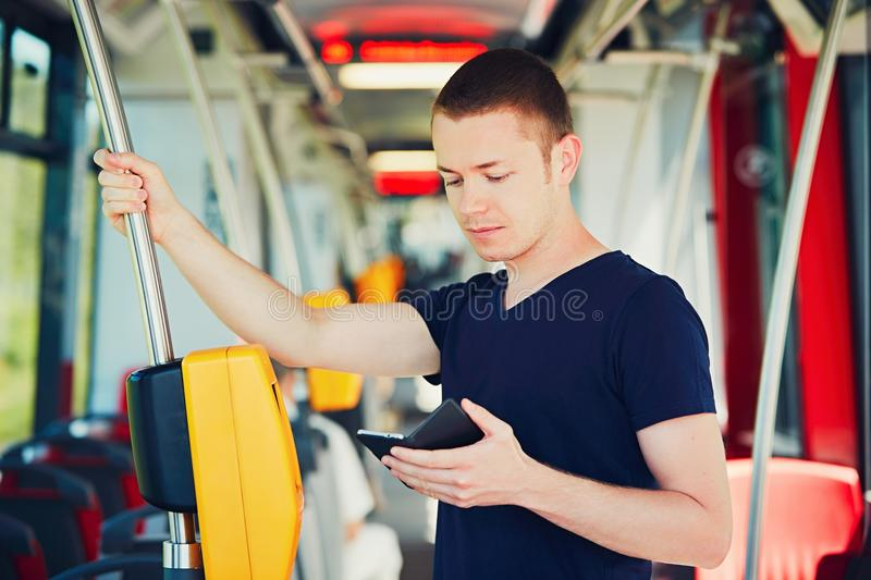 Traveling by public transport. Everyday life and commuting to work by bus (tram). Handsome man is paying transport ticket with mobile phone royalty free stock photo