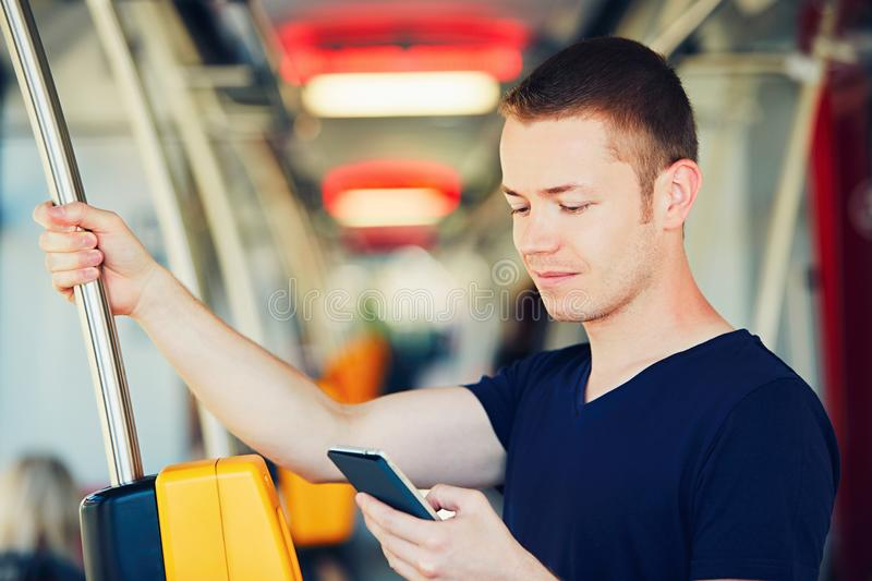 Traveling by public transport. Everyday life and commuting to work by bus (tram). Handsome man is paying transport ticket with mobile phone stock photos