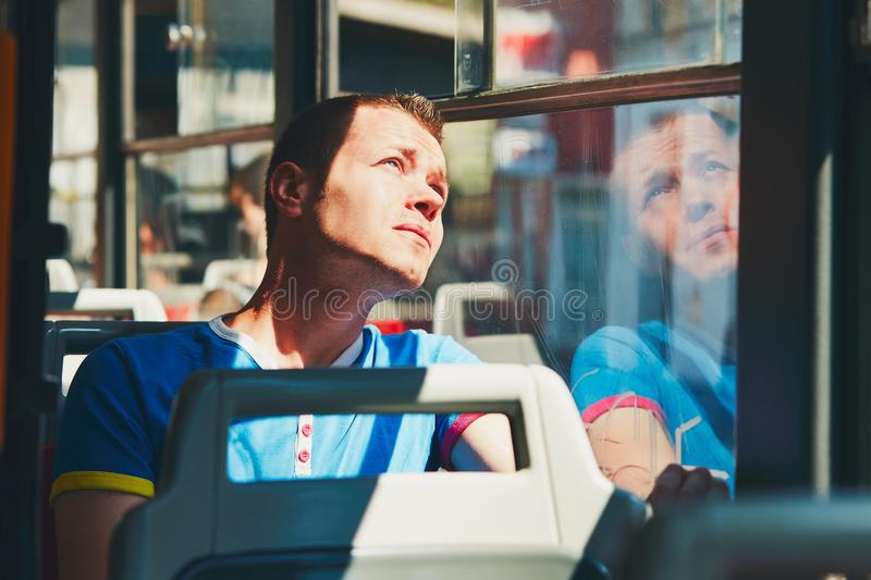 Traveling by public transport. Everyday life and commuting to work by public transportation. Handsome young man is traveling by tram (bus royalty free stock images