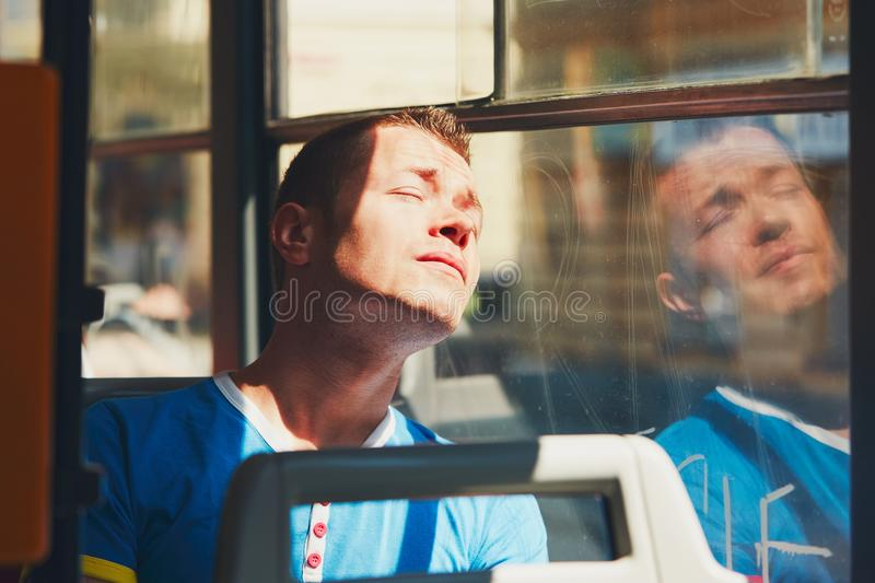 Traveling by public transport. Everyday life and commuting to work by public transportation. Handsome young man is traveling by tram (bus). Tired man in hot day royalty free stock photo