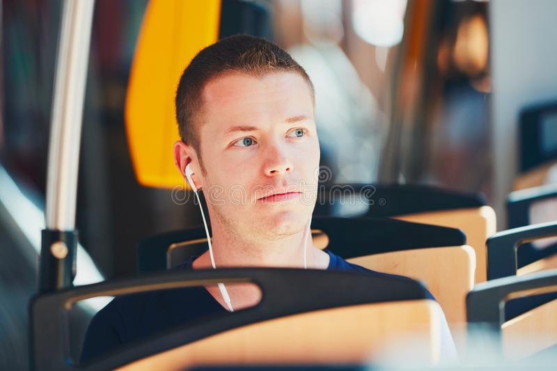 Traveling by public transport. Everyday life and commuting to work by public transportation. Handsome young man is traveling by tram. Man is wearing headphones royalty free stock photo