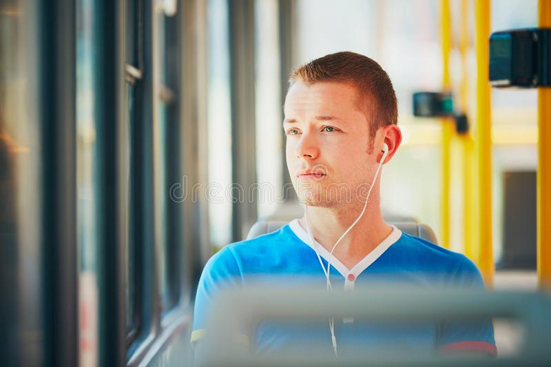 Traveling by public transport. Everyday life and commuting to work by public transportation. Handsome young man is traveling by tram (streetcar). Man is wearing stock images