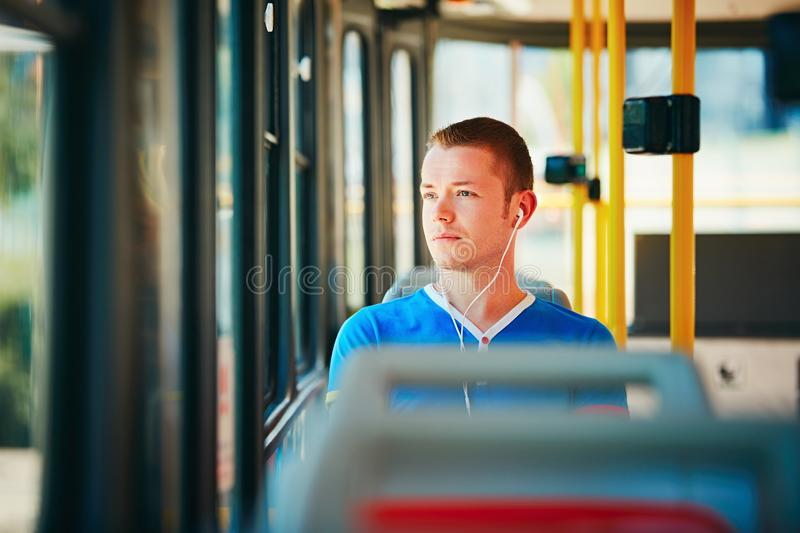 Traveling by public transport. Loneliness man is wearing headphones and listening to music. Everyday life and commuting to work by public transportation stock photo