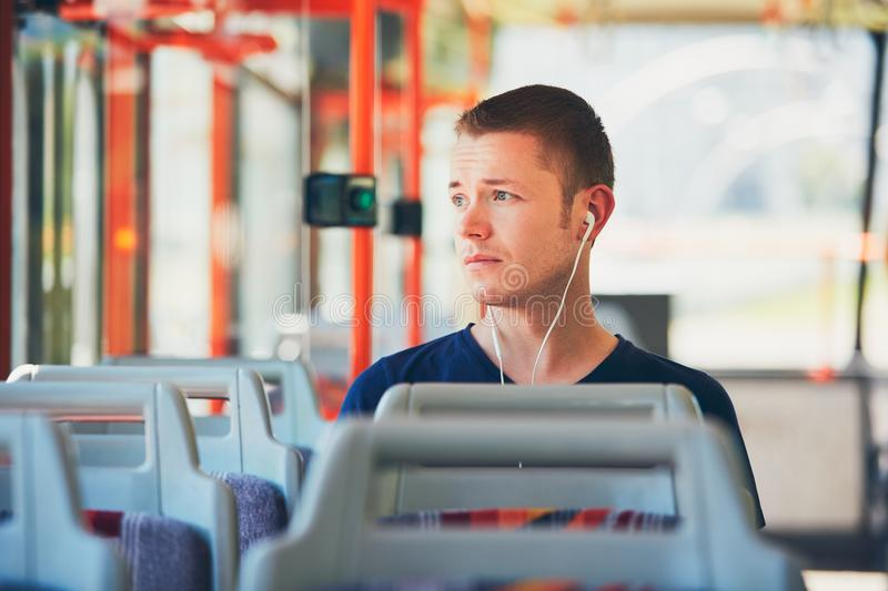 Traveling by public transport. Sad young man is traveling by tram (bus). Everyday life and commuting to work by public transportation. Man is wearing headphones royalty free stock photo