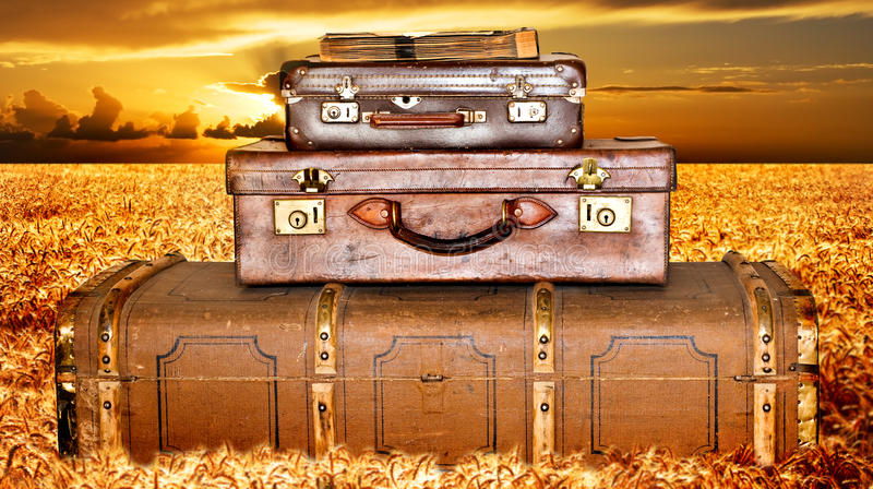 Traveling suitcases in a wheat field at sunset. Traveling suitcases stacked up in a wheat field at sunset stock image