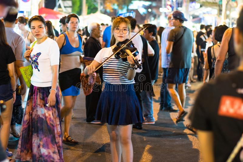 Traveling through Thailand. Chiang Mai, Thailand 9 April 2017 : Young woman playing vintage violin in the streets of Chiang Mai in Thailand royalty free stock photo