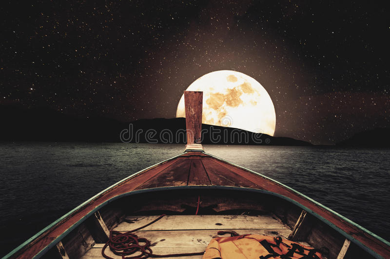 Traveling on wooden boat at night with full moon and stars on sky. scenic panorama with full moon on sea at night, vintage tone. Traveling on wooden boat at royalty free stock photography