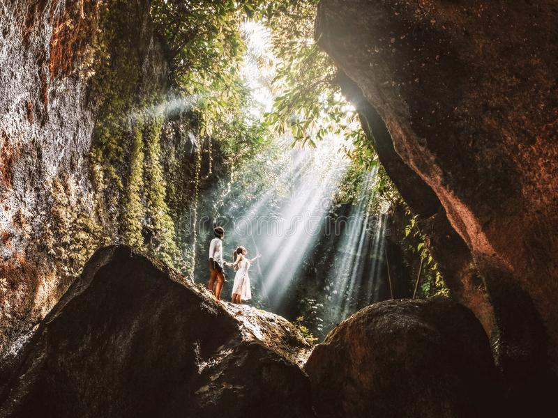 Traveling young couple with tropical rainforest rock in Bali enjoying life at beautiful Lighting hidden waterfall royalty free stock photography