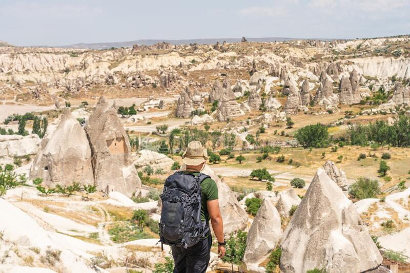 A traveller with backpack  looking to Cappadocia landscape, Goreme town in Anatolia, Turkey. Asia stock photo