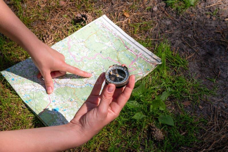 Traveller check con l'itinerario facendo uso di una mappa e di una bussola fotografia stock libera da diritti