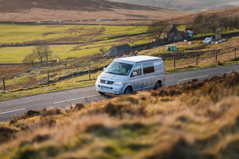 DERBYSHIRE, UK - 31ST MARCH 2019: A silver van drives through the Peak District during a low sunset royalty free stock image