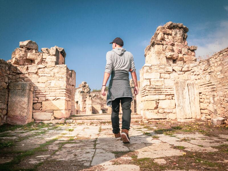 Traveller enjoys the views. Male person is steping into historical site with greek building ruins around. Concept of solo exploration of historical places stock image