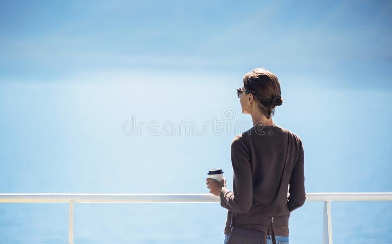 Traveller girl standing on ferry boat, looking at the sea and holding a coffee cup, travel and active lifestyle concept royalty free stock photography