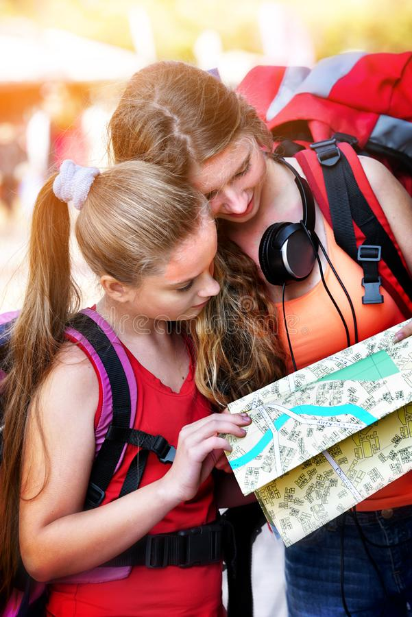 Traveller girls with backpack looking for way tourist paper map stock photo