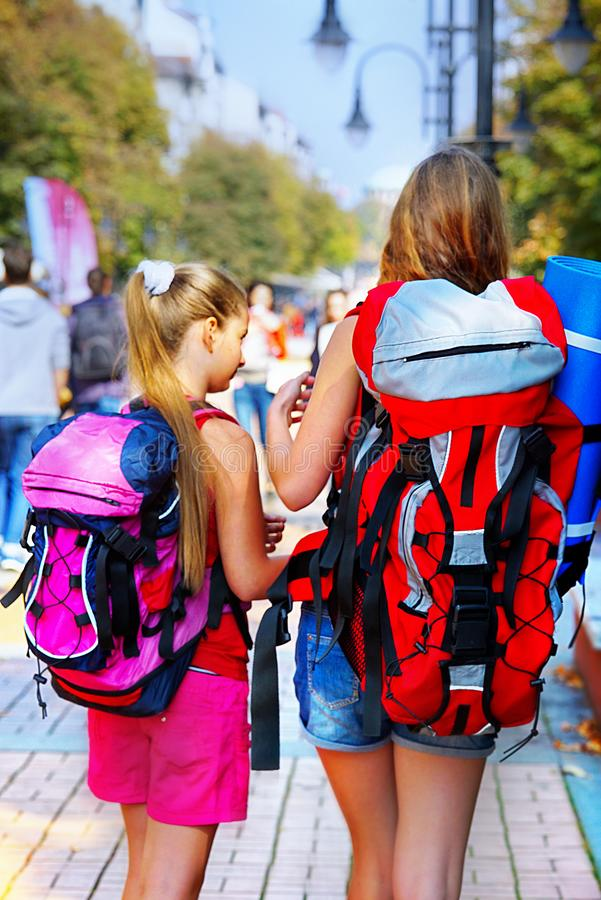 Traveller girls with backpack search way by tourist paper map royalty free stock images