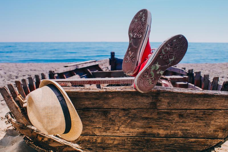 Traveller in red shoes laying in the old boat and resting. stock photos