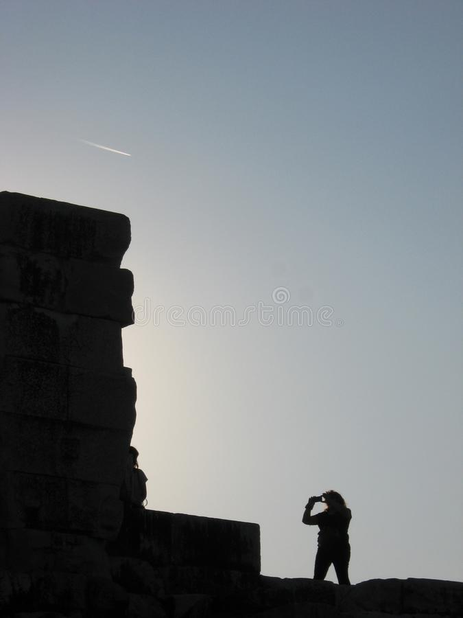 Traveller silhouette takes a picture near ancient wall royalty free stock images