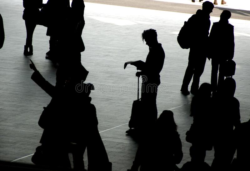 Travellers silhouetted on station concourse. Traveller with suitcase stands alone on station concourse, silhouetted against bright light spilling in from the royalty free stock images