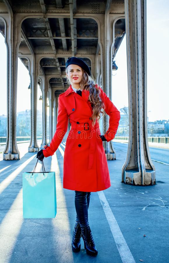 Traveller woman on bridge in Paris holding shopping bag. Bright in Paris. Full length portrait of young traveller woman in red trench coat on Pont de Bir-Hakeim stock photos