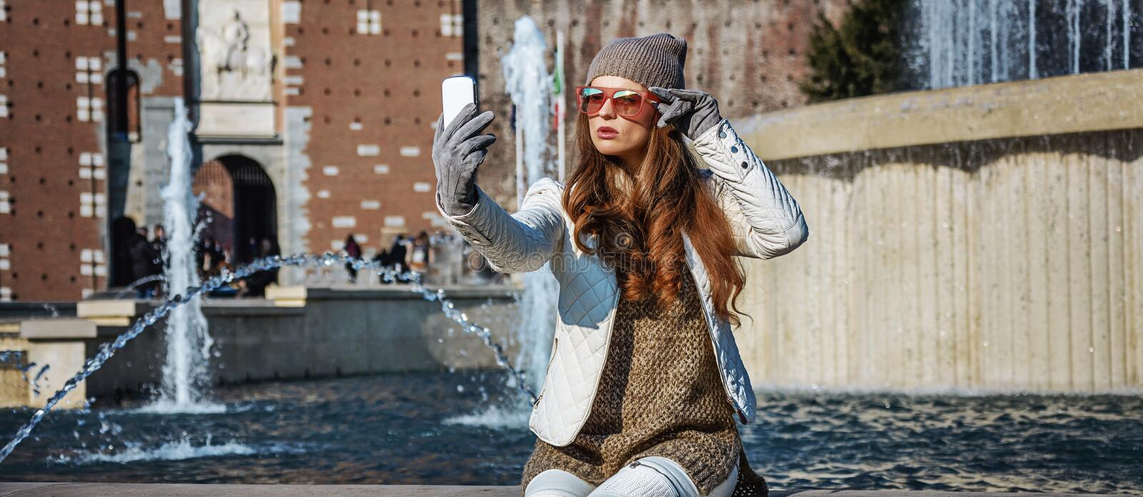 Traveller woman in Milan, Italy taking selfie with smartphone. Rediscovering things everybody love in Milan. young traveller woman in Milan, Italy with stock photos