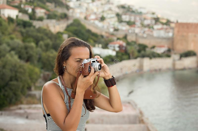Traveller woman photographing with vintage camera. Portrait of a traveller brunette woman photographing using a vintage camera and wearing top with black and stock photography