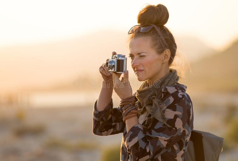 Traveller woman taking photos with retro photo camera. Adventure traveller woman in hiking clothes taking photos with retro photo camera against mountain and sea stock image