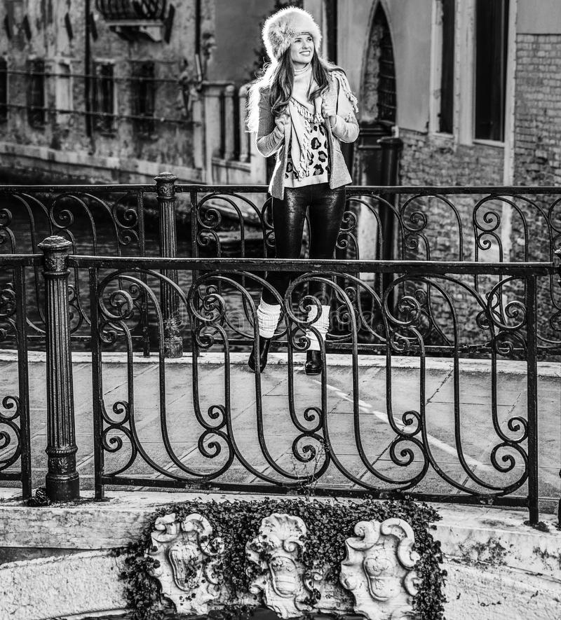 Traveller woman in Venice, Italy looking into the distance. Venice. Off the Beaten Path. Full length portrait of smiling young traveller woman in fur hat in royalty free stock photos
