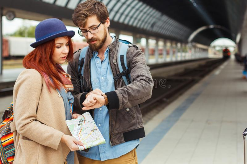 Hipster Traveller couple looking at smart watch while waiting for the train at railway station. Autumn time. Woman stock image