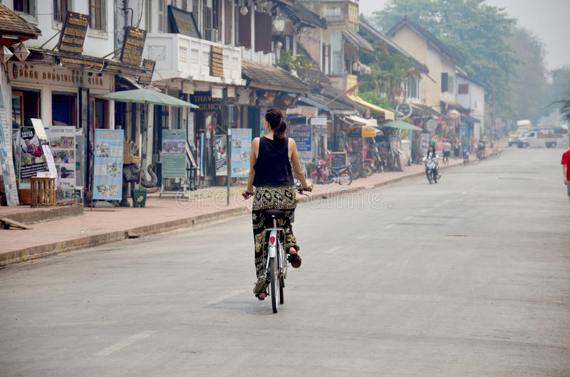 Traveller women use bicycle for biking visit and sightseeing around ancient city of Luang Prabang stock photos