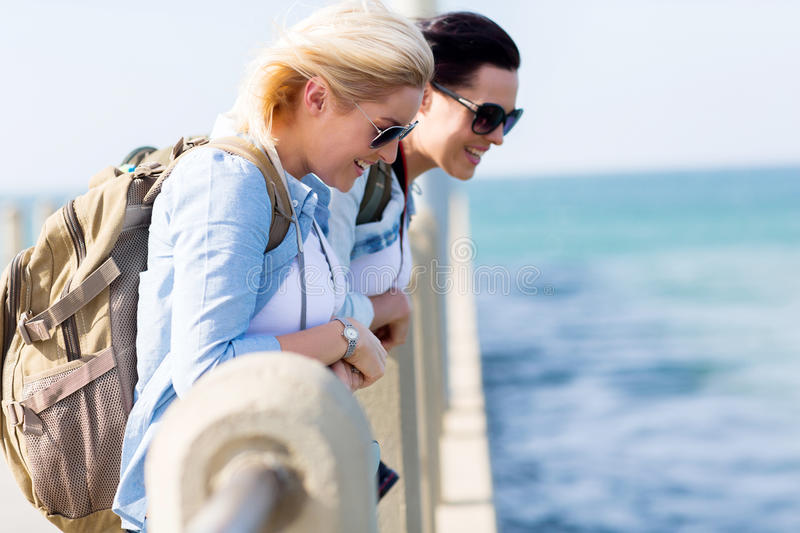 Travellers beach pier. Two beautiful travellers standing on pier looking at the sea water royalty free stock image
