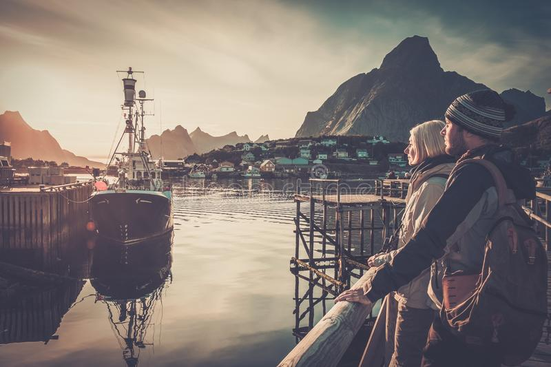 Travellers couple in Reine village, Norway. Young travellers couple looking at sunset in Reine village, Norway stock photography