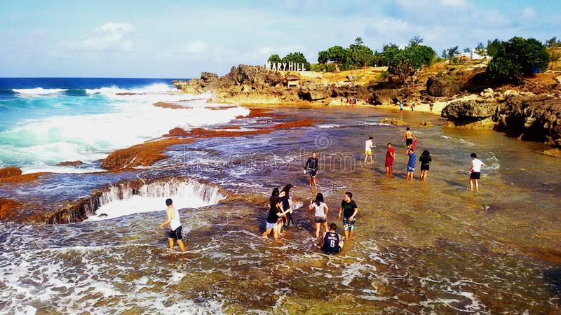 Travellers enjoying the foamy clear water. Location: Death Pool, Pangasinan Philippines. People, rock, formation, hole, ocean, waves, seacape royalty free stock images