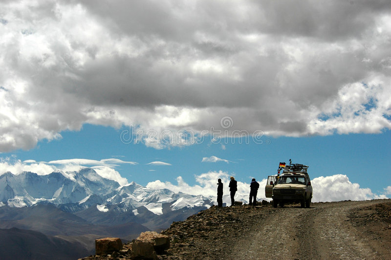 The travellers on the mountain top. The travellers with a jeep reach the mountain top and have a rest by the road,Tibet,China royalty free stock photography