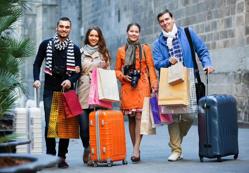 Travellers with shopping bags on street. Young smiling travellers with shopping bags on city street stock image