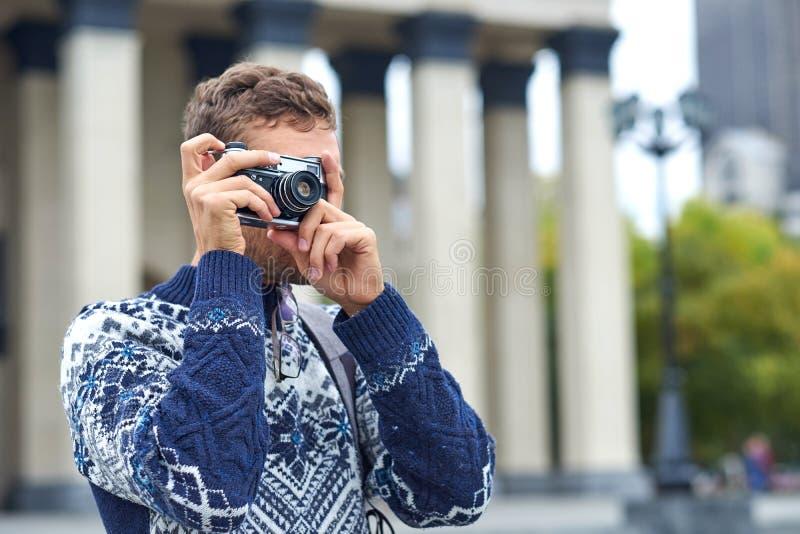Travellers tourisme de l'Homme du voyage photographier avec caméra rétro dans une ville à l'architecture ancienne photo libre de droits