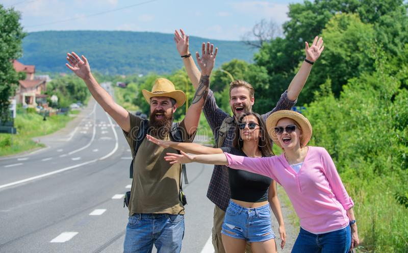 Travellers try to stop car. Friends hitchhikers travelling summer sunny day. Company friends travelers hitchhiking at royalty free stock images