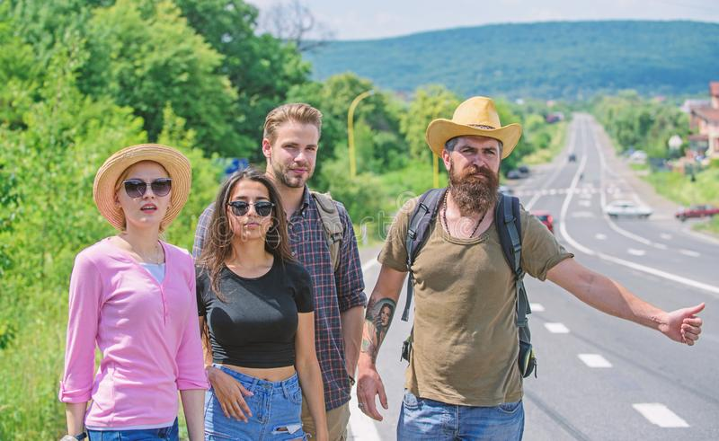 Travellers try to stop car. Friends hitchhikers travelling summer sunny day. Company friends travelers hitchhiking at stock photos