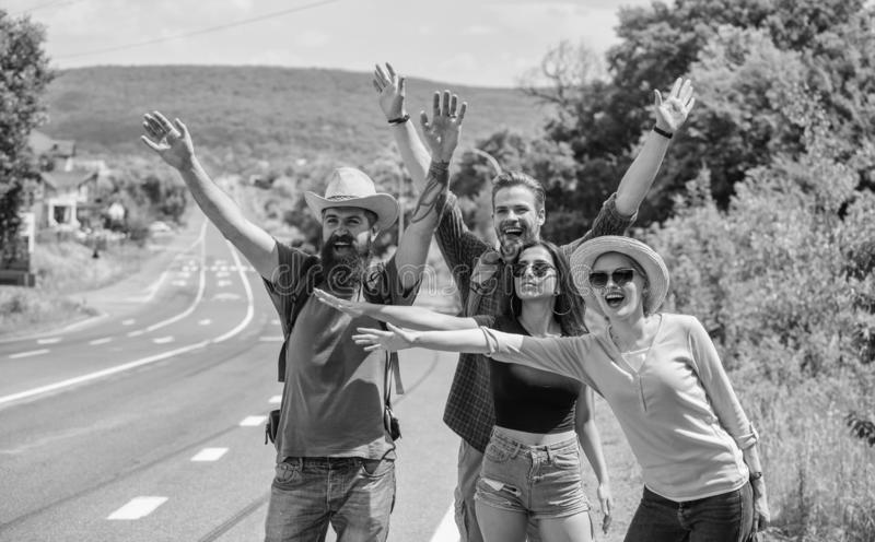 Travellers try to stop car. Friends hitchhikers travelling summer sunny day. Company friends travelers hitchhiking at stock photo