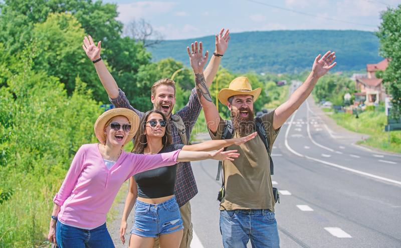 Travellers try to stop car. Friends hitchhikers travelling summer sunny day. Company friends travelers hitchhiking at. Edge road nature background. Begin great stock photos
