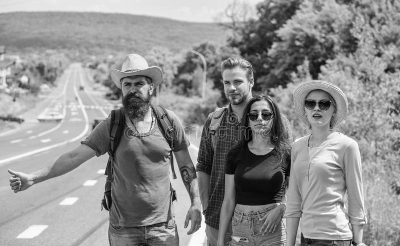 Travellers try to stop car. Friends hitchhikers travelling summer sunny day. Company friends travelers hitchhiking at. Edge road nature background. Begin great stock photo